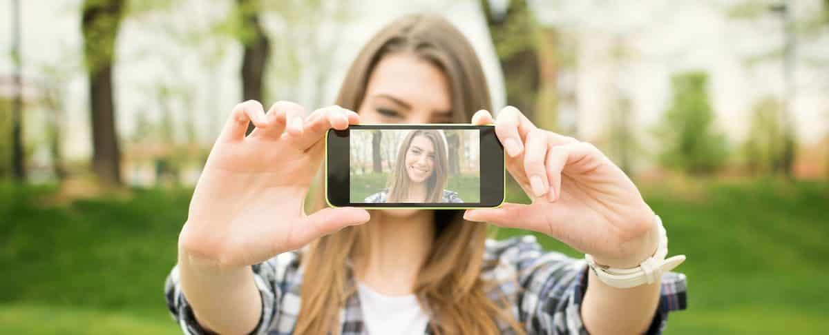 Cute Caucasian brunette teenage woman taking a selfie photo outdoors on sunny summer day in park using her smart phone. Modern youth lifestyle concept.