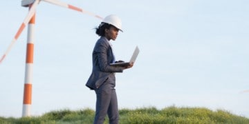 Wind turbine operation & maintenance. Engineer woman working on laptop next to wind turbines.