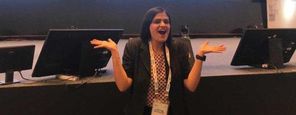 SWE member Riya Thakkar in front of stage