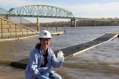 Becky Svatos sampling water from the Mississippi River