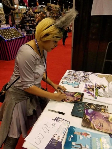Author Eve L. Ewing signing her Ironheart comic books