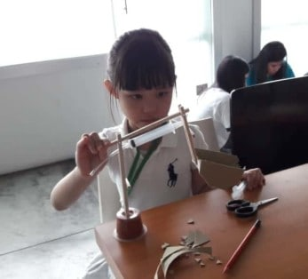 Young girl builds an hydraulic-powered crane