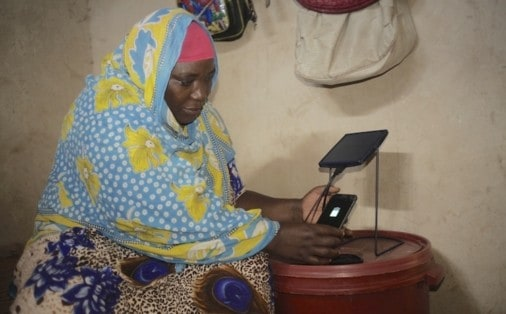 woman charging her phone with solar equipment at Kizimkazi village in Zanzibar, Tanzania