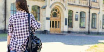 young woman walking toward college building