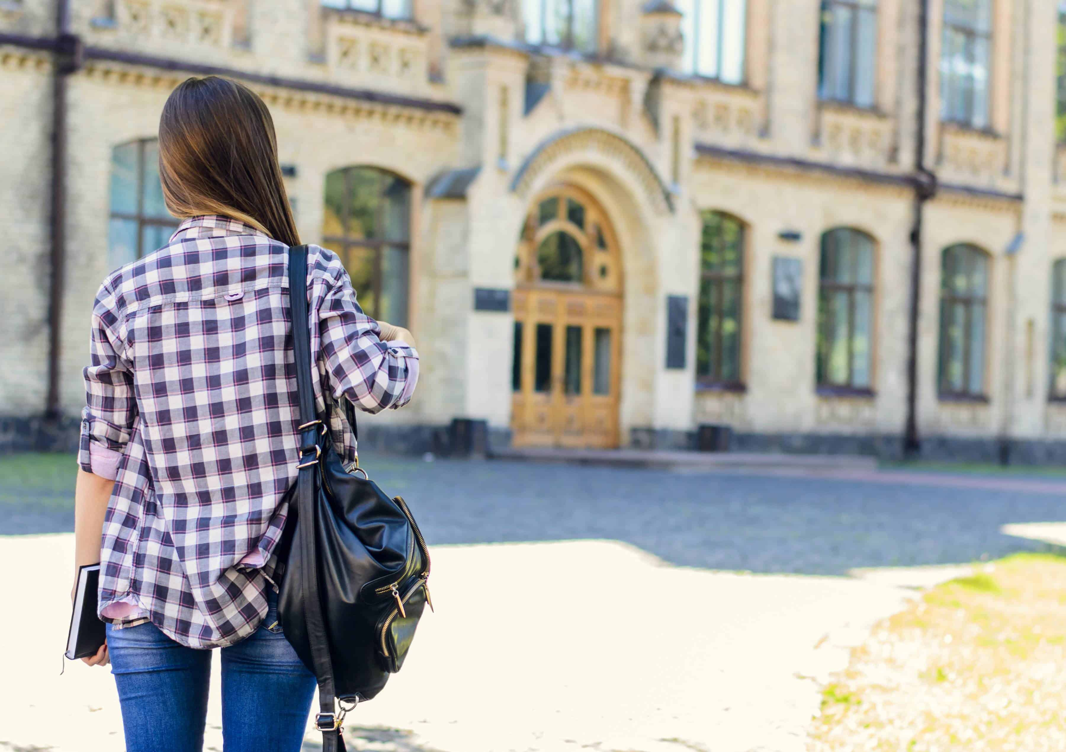 young woman walking toward college building