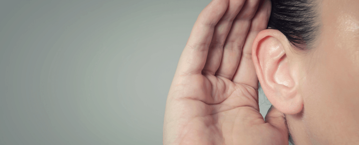 close-up of hand cupped around listening ear