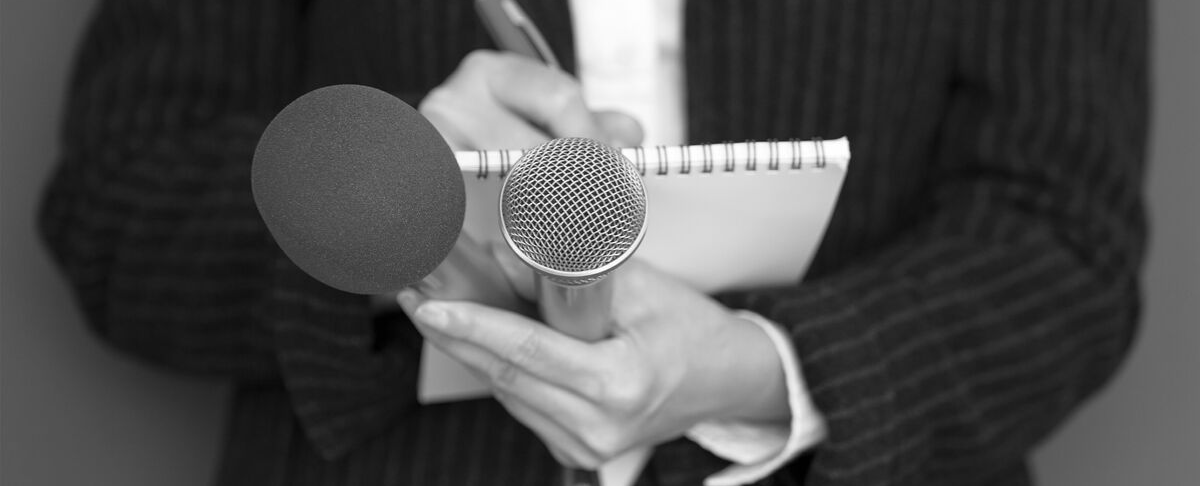 close-up image of media reporter holding microphone and pen and paper