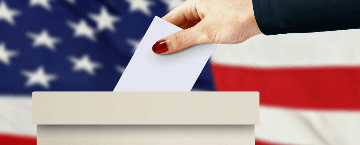 image of woman's hand putting vote into ballot box with American flag in background