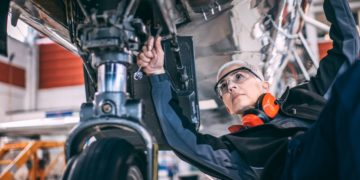Senior female mechanic using a socket wrench while repairing or doing maintenance to the landing gear of a small airplane in an aircraft maintenance hangar.
