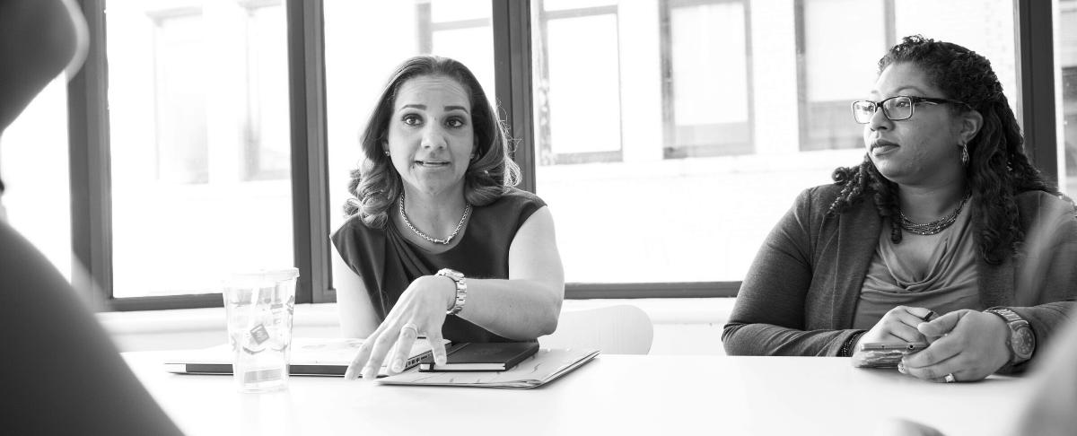 women speaking across table