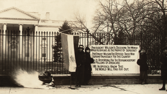 Positioned in front of the White House, National Woman's Party members burned copies of President Wilson's speeches, challenging the inconsistency between his support for democracy overseas, but failure to embrace equality for women at home.
