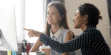 young asian woman mentoring young caucasian woman